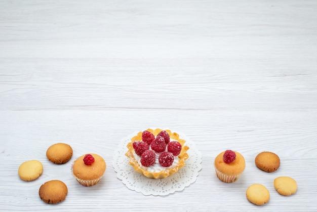 軽い机の上のクッキーと一緒にラズベリーとおいしい小さなケーキ、ケーキビスケットスイートベリー