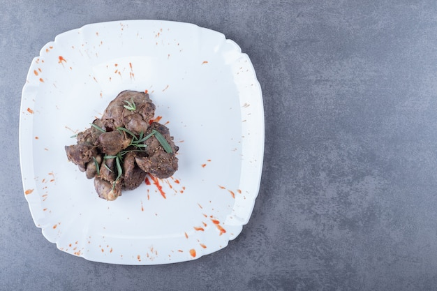 Delicious liver kebab on white plate.