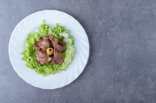 Вкусный кебаб из печени с салатом на белой тарелке.