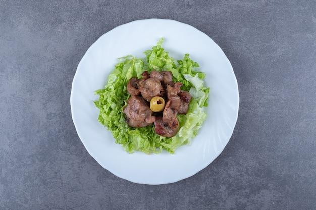 Delizioso kebab di fegato con lattuga sul piatto bianco.