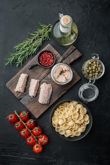Вкусная паста lumaconi с тунцом и молодыми каперсами на черном, вид сверху