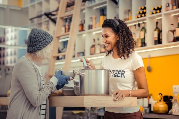 美味しいランチ。鍋を持ちながらホームレスの女性にスープを与える肯定的な素敵な女性