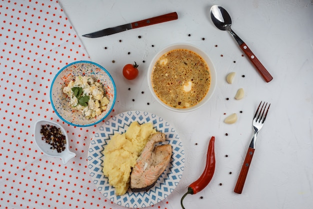 Delicious lunch set contains mashed potatoes with red fish steak, salad and soup with sour cream topping. dishes are serves on the white background with pepper and garlic.