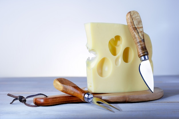 Delicious maasdam cheese on wooden board with copy space