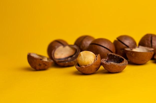 Вкусные орехи макадамия на желтом фоне