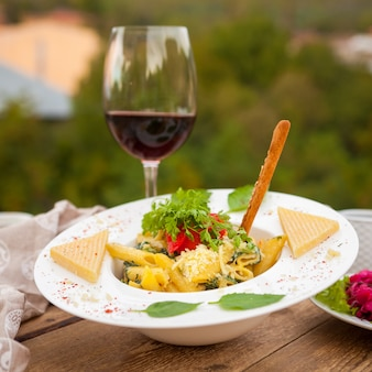 Delicious macaroni mixed with salad with wine and cheese in a plate with village on background, side view.