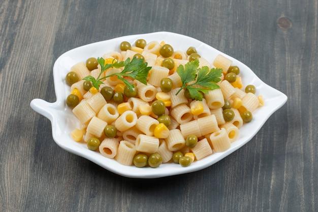 Deliziosi maccheroni con piselli e verdure su un tavolo di legno