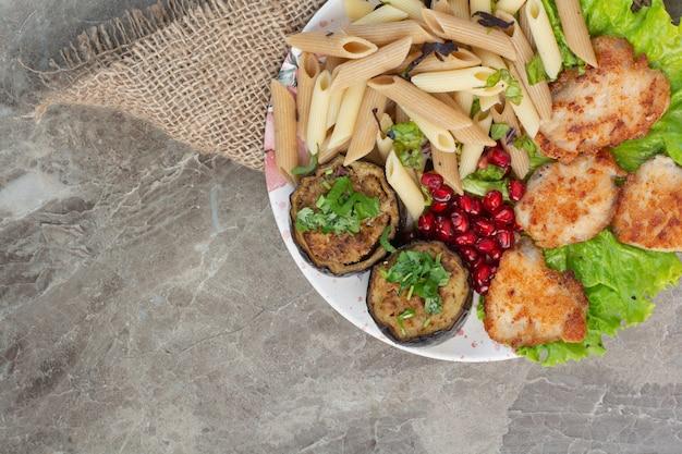 Вкусные макароны с гранатом и салатом на белой тарелке.