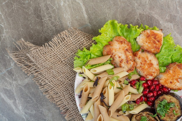 Delicious macaroni with pomegranate and lettuce on white plate.