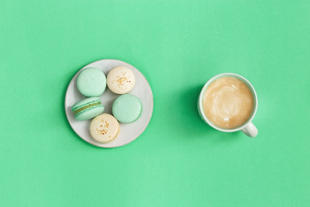 Delicious macarons and hot coffee cappuccino in big mug on bright blue background