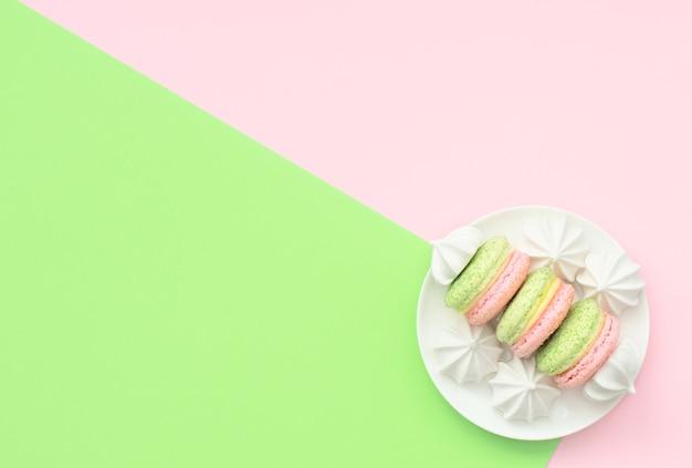 Вкусные макароны с белыми меренге на белой тарелке на двойном зеленом и розовом фоне