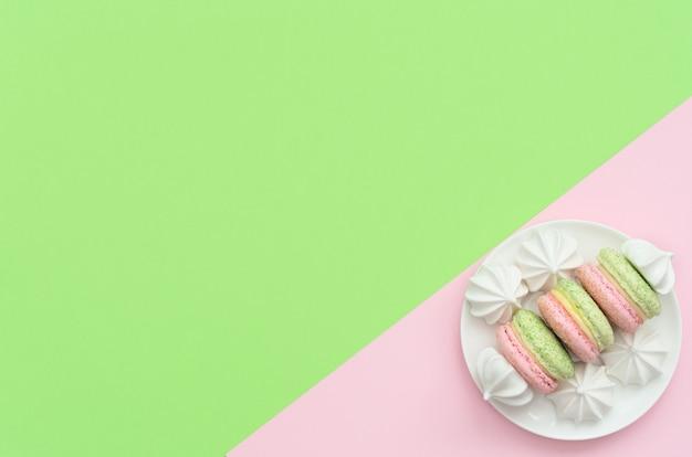 Вкусные макароны с белыми меренге на белой тарелке на двойном зеленом и розовом фоне.