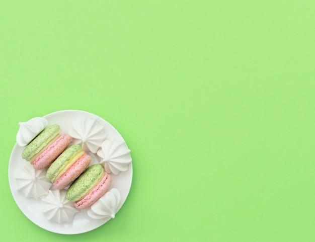 Вкусные макароны с белыми меренге на белой тарелке на зеленом фоне