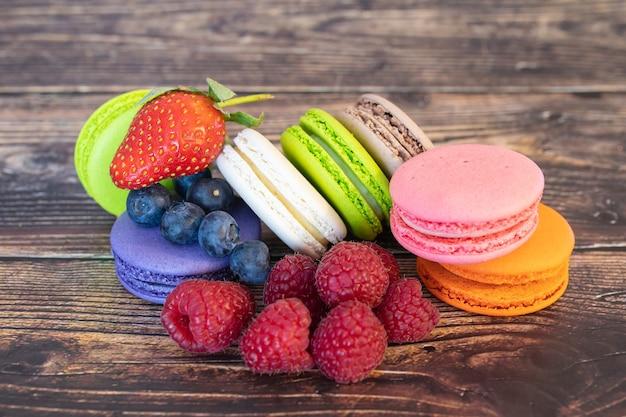 Вкусные миндальное печенье и лесные ягоды, черника и малина на деревянной поверхности