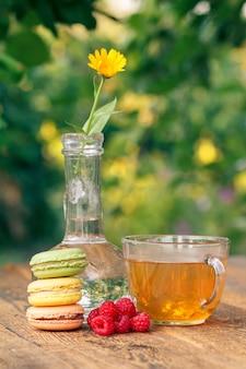 다양한 색상의 맛있는 마카롱 케이크, 유리 플라스크에 줄기가 있는 금송화 꽃, 흐릿한 자연 배경을 가진 나무 판자에 녹차 한 잔