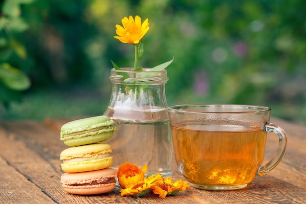 다양한 색상의 맛있는 마카롱 케이크, 유리병에 줄기가 있는 금송화 꽃, 흐릿한 자연 배경을 가진 나무 판자에 녹차 한 잔