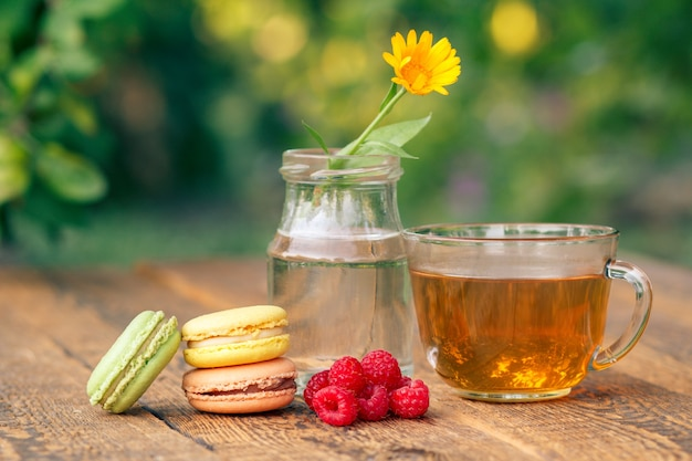 다양한 색상의 맛있는 마카롱 케이크, 유리병에 줄기가 있는 칼렌듈라 꽃, 흐릿한 자연 배경의 나무 판자에 신선한 라즈베리, 녹차 한 잔