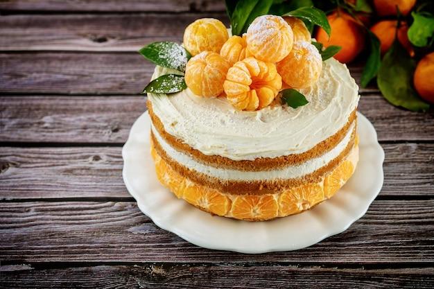 Вкусный мандариновый или апельсиновый бисквит, украшенный свежим мандарином. деревенский фон.