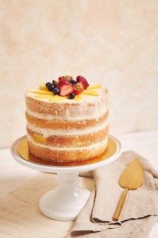 Delicious mango strawberry summer naked cake on a white table with white