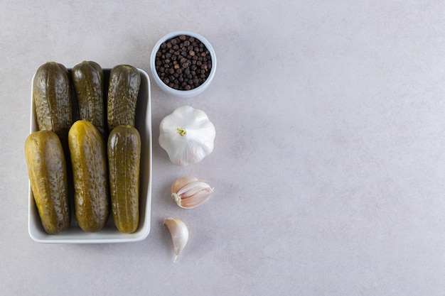 Delicious marinated pickled cucumbers placed on stone background .