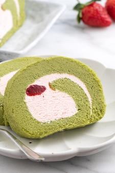 흰색 바탕에 딸기 아이싱 크림을 얹은 맛있는 말차 스위스 롤 케이크 조각을 닫습니다.