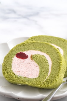 Delicious matcha swiss roll cake slices with strawberry icing cream