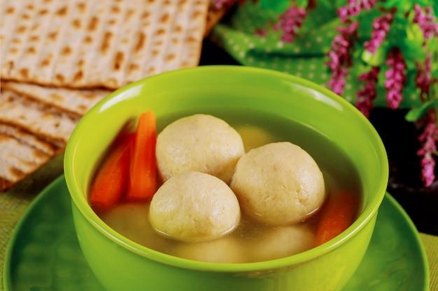 Delicious matzo ball soup with carrot and matzos bread. close up.