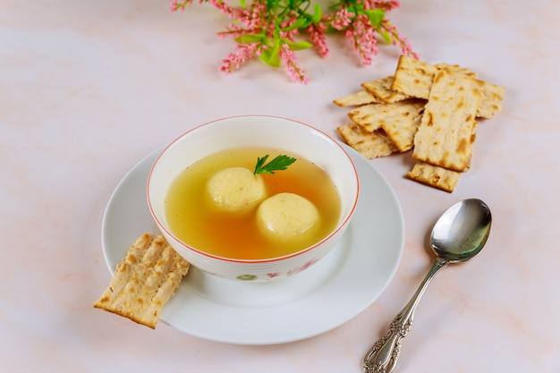 Delicious matzo ball soup with carrot and matzos bread.