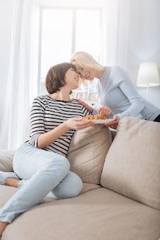 맛있는 식사. 함께 아침 식사를하면서 미소하고 크로와상과 함께 접시를 들고 기쁘게 긍정적 인 레즈비언 커플
