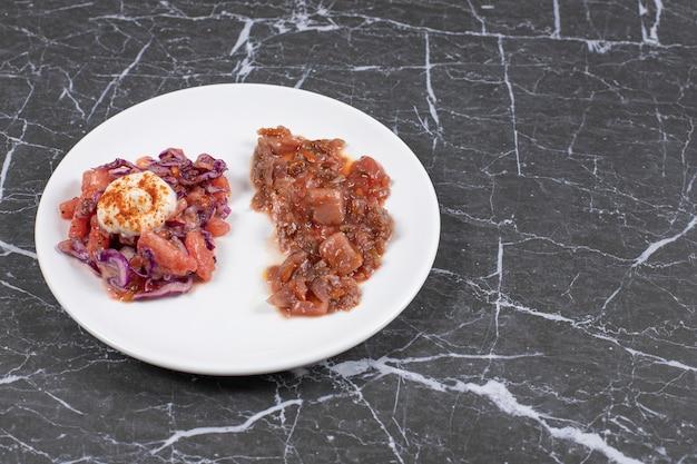 大理石の白いプレートに肉を添えた美味しいお食事。
