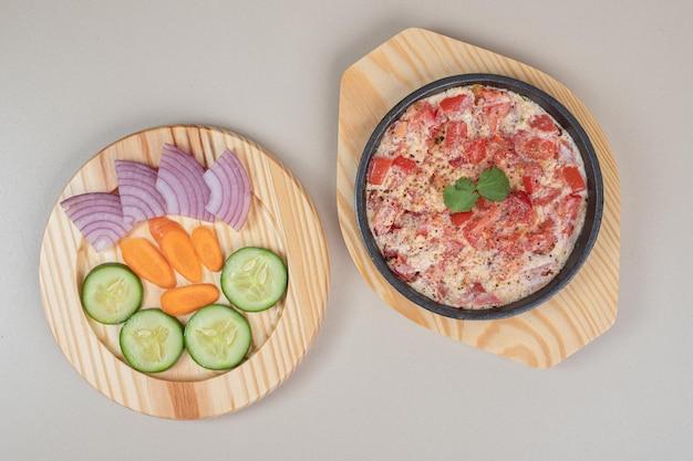 木の板に野菜をスライスした美味しいお食事。
