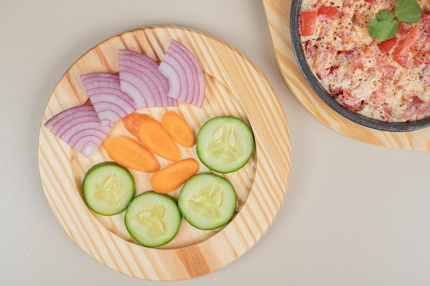 Delizioso pasto con verdure a fette su tavola di legno.