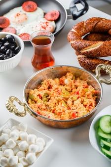 Вкусные блюда на сковороде и в горшочке с салатом, солеными огурцами, турецким бубликом, чашкой чая под высоким углом зрения на белой поверхности