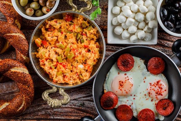Вкусные блюда в горшочке и сковороде с турецким бубликом, соленые огурцы на деревянной поверхности