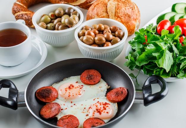 Вкусные блюда в горшочке с чашкой чая, турецким бубликом, помидорами, зеленью под высоким углом зрения на белой поверхности