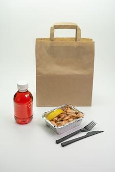 매일 배달되는 맛있는 식사. 피트니스 음식, 야채, 고기 및 모스, 호일 상자에 설탕에 절인 과일, 흰색 배경에 종이 봉투에 칼 붙이