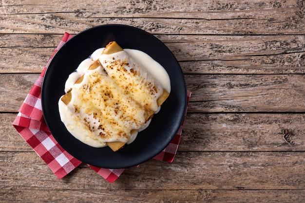 Вкусные мясные макароны каннеллони на деревянном столе