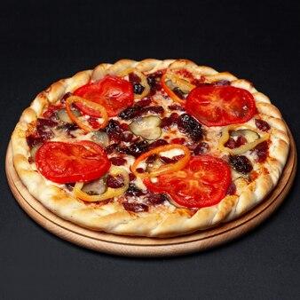 黒に分離された木製のプレートで提供していますおいしい肉ピザ