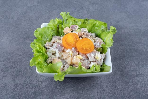 Вкусный мясной салат в белой миске.