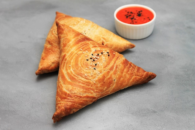Delicious meat samosas and red sauce on gray.
