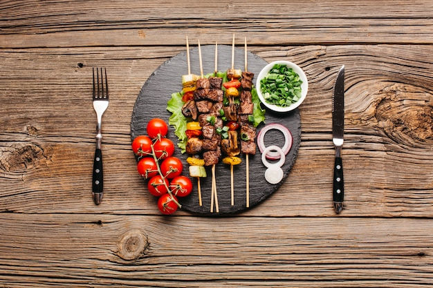 Delicious meat skewer on black slate with fork and butter knife over wooden table