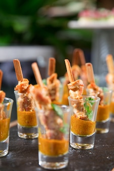 Delicious meat snacks with sauce in shot glasses