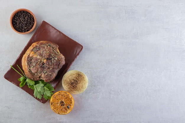 Delicious meat with sliced lemon and pepper corns background