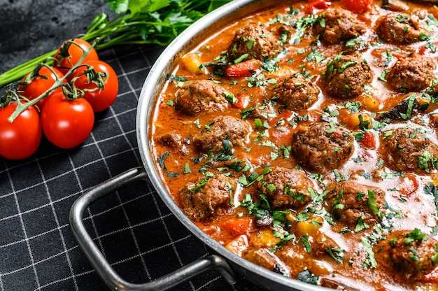 Delicious meatballs made from ground beef in tomato sauce, served in old metal pan. black surface. top view