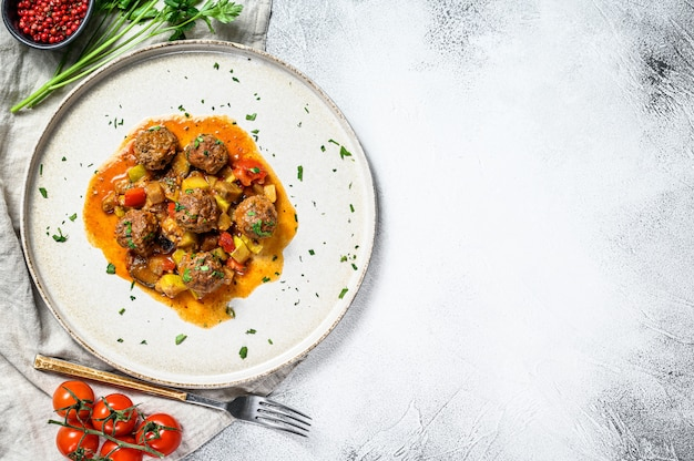 Delicious meatballs made from ground beef in tomato sauce, served in old metal pan. gray background,. top view. space for text