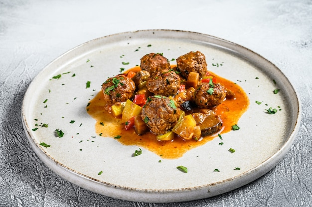 Delicious meatballs made from ground beef in tomato sauce, served in old metal pan. gray background. top view
