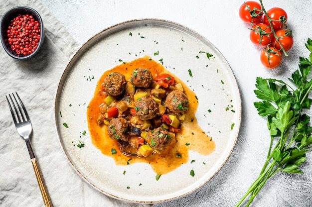 Delicious meatballs made from ground beef in tomato sauce, served in old metal pan. top view