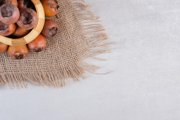 Вкусные плоды мушмулы в деревянной миске. фото высокого качества