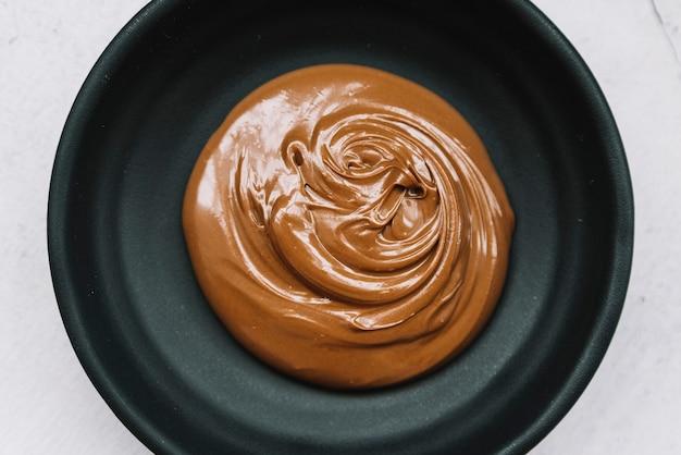 白い背景の上に黒いボールでチョコレートを溶かしたおいしい