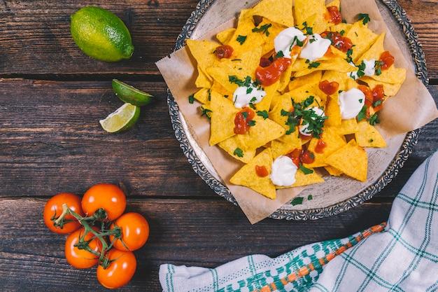 Вкусные мексиканские начос в тарелке; ломтики лимона; помидоры черри и скатерть на столе